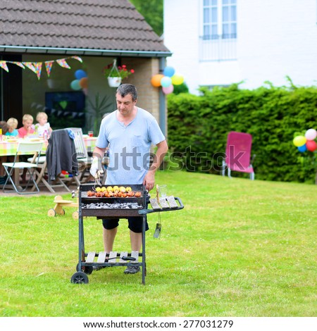 People enjoying summertime. A man cooking meat on barbecue for summer family dinner at the backyard of the house.