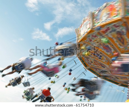 People enjoying the ride in a classic Chair-O-Planes at the fair