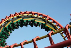 People enjoying the thrill of a roller coaster going through a loop at high speed on a clear summer day.