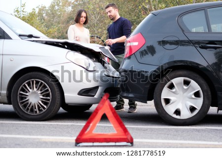 People examining car body damages after car hit