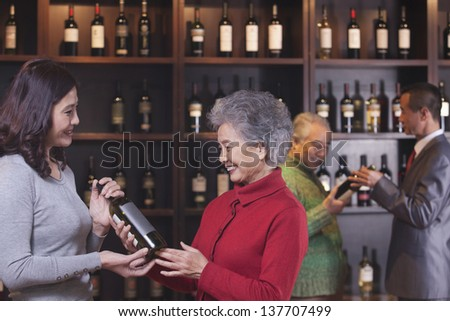 People Examining Wine Bottles, Two Women in the Foreground