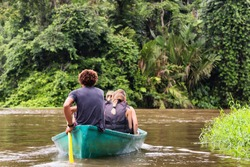 People exploring a wild nature area by rowing boat. Ecotourism concept. Tortuguero national park. Costa Rica.