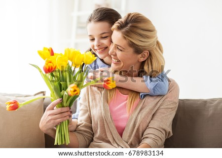 people, family and holidays concept - happy girl giving tulip flowers and hugging her mother at home #678983134
