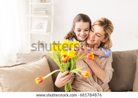 people, family and holidays concept - happy girl giving tulip flowers and hugging her mother at home #681784876
