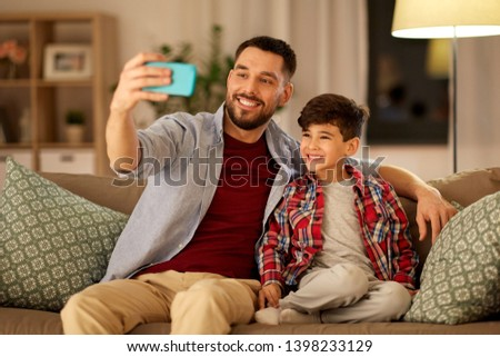 people, family and technology concept - happy father and little son taking selfie by smartphone sitting on sofa at home in evening