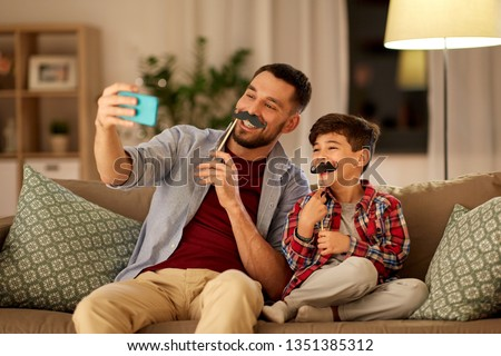 people, family and technology concept - happy father and little son with mustaches party props taking selfie by smartphone sitting on sofa at home in evening