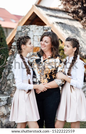 People, family and teens concept - twin sisters with their mom. Twin sisters embracing their mother with smiles.  Beauties in style. School graduates in uniform