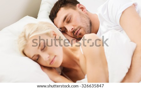 people, family, bedtime and happiness concept - happy couple sleeping and hugging in bed at home