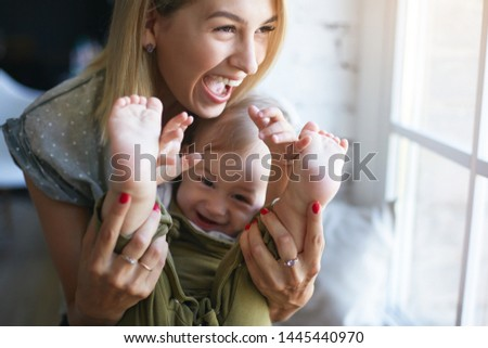 People, family, happy childhood, joy and love concept. Cheerful attractive young woman holding feet of her cute baby son, opening mouth widely in excitement, having fun indoors. posing by window