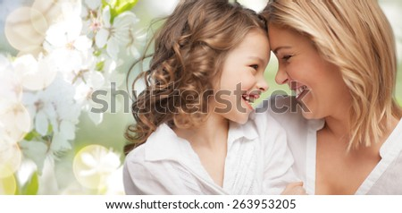 people, family, love and harmony concept - happy mother and daughter cuddling over green summer garden background
