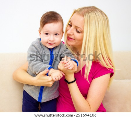 people, family, motherhood and children concept - happy mother hugging adorable baby