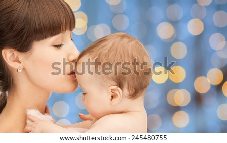 people, family, motherhood and children concept - happy mother hugging adorable baby over blue lights background