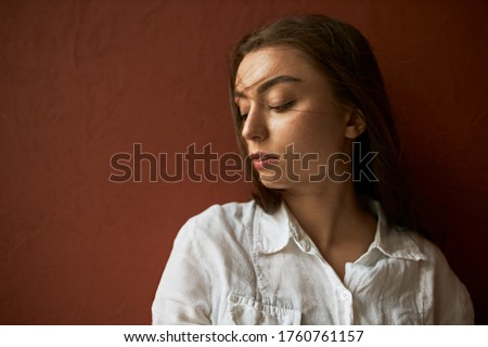 People, femininity and beauty concept. Close up shot of attractive serious young Caucasian woman in white shirt looking down with shy timid smile, advertising hair care products, posing isolated stock photo