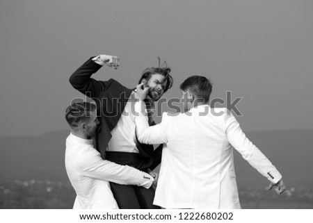 people fighting with energy in nature on blue sky background, young men in business outfit on wedding fight, marketing and fashion