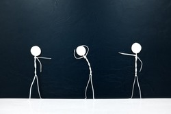 People figures pointing fingers on a scared stick man  on a dark background. Bullying, victim blaming, accusation and abuse concept.