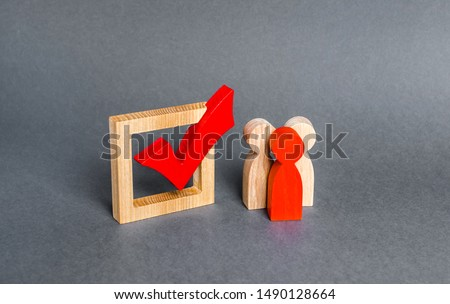 People figurines stand near the checkbox for voting in democratic elections. Lobbying interests, voter bribery, and rigging presidency or parliamentary election results. expression of will