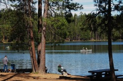 People fishing on the banks and in boats at South Twin Lake in the Deschutes National Forest in Central Oregon on a spring day.