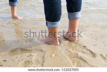 people fold pants for  walk on the beach #512027005