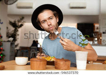 People, food and lifestyle concept. Indoor shot of attractive young student wearing black hat and blue t-shirt appeasing his hunger, having vegetables during lunch break at modern restaurant