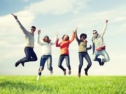 people, freedom, happiness and teenage concept - group of happy friends in sunglasses jumping high over blue sky and grass background