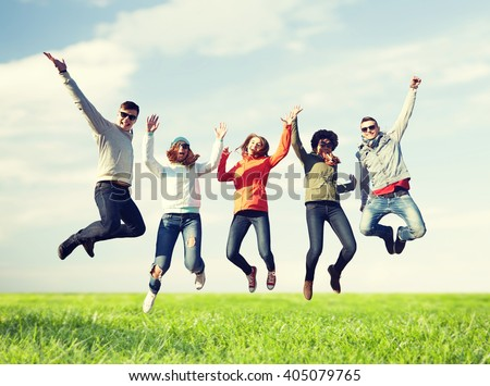 people, freedom, happiness and teenage concept - group of happy friends in sunglasses jumping high over blue sky and grass background #405079765