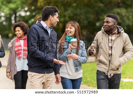 people, friendship, communication and international concept - group of happy friends walking along autumn park and drinking coffee #551972989