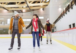 people, friendship, sport and leisure concept - happy friends on skating rink