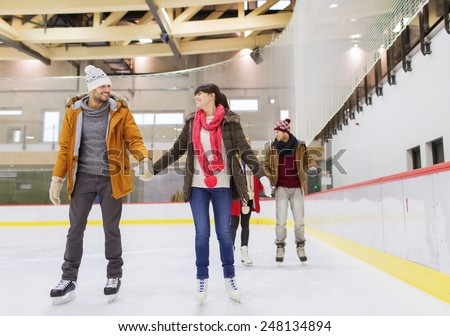 people, friendship, sport and leisure concept - happy friends on skating rink #248134894