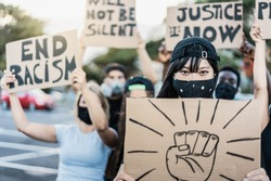 People from different culture and races protest on the street for equal rights wearing protective masks - Focus on asian girl face