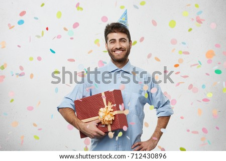 People, fun and celebration concept. Picture of handsome happy young bearded businessman wearing cone hat celebrating his anniversary with colleagues, grinning broadly, showing perfect white teeth