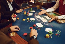 People gamble at a poker table in a casino.