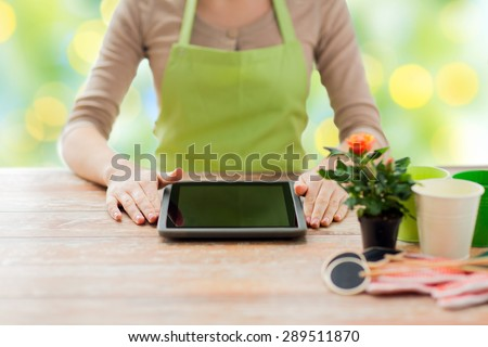 people, gardening, flowers and profession concept - close up of woman or gardener with tablet pc computer sitting at wooden table over green lights background