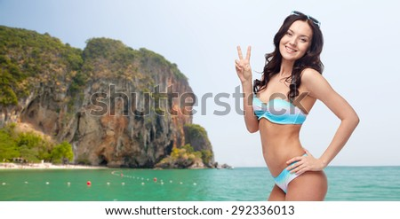 people, gesture, summer, beach and fashion concept - happy woman in bikini swimsuit showing victory hand sign over sea and rock background