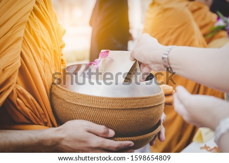 People give alms to buddhist monk when New year is coming. It is Asian traditional. Person offer food and put in monk alms bowl. People do good thing to create positive karma for themself, make merit Foto stock ©
