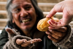 people give bread or sharing food to poor and homeless man to help his hungry for charity