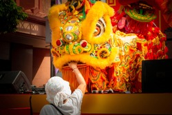 People give money through lion mouth for lucky, wealthy and happiness in Chinese New Year Festival at Chinatown, Yaowarat. Traditional lion dance parade at shrine.