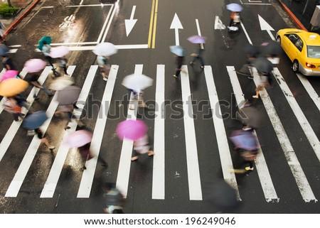 People go across the street in the rain.