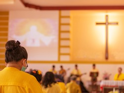 People go to church for Sunday prayers in Yellow theme.people wearing masks, praying, and standing apart,new normal,social distancing,Coronavirus outbreak and coronaviruses influenza.