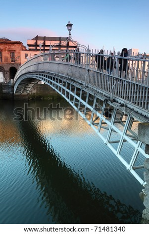 People going on Ha'penny Bridge, Liffey River in Dublin, Ireland