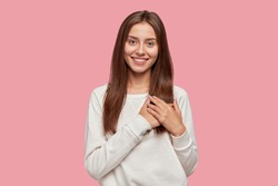 People, gratitude, positive feeling concept. Satisfied generous brunette woman with tender smile, keeps both palms on chest, wears casual sweater, stands against pink background, being kind hearted