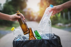 people hand holding garbage bottle plastic and glass putting into recycle bag for cleaning