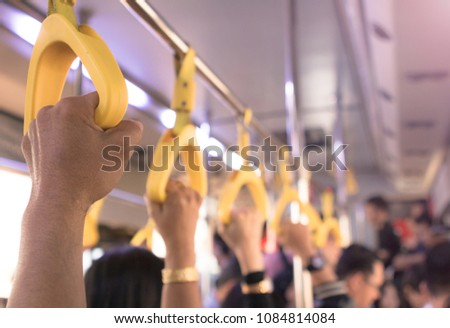 People hand holding handle on the bus gate #1084814084