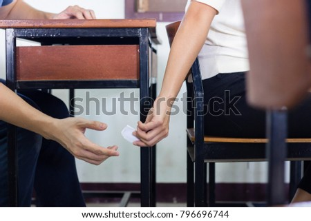 People hand sending a piece of answer paper during exam in class room