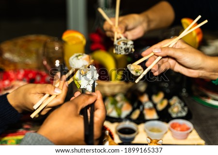 People hands hold sushi rolls with sticks. Couples eating and sharing sushi roll, maki, nigiri, uramaki. Food concept. Focus on first chopstick.