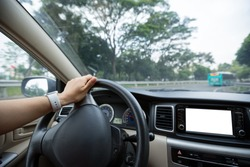 People hands holding steering wheel while driving car on city road