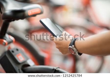 People hands using smartphone scanning the QR code of shared bike in city #1252425784