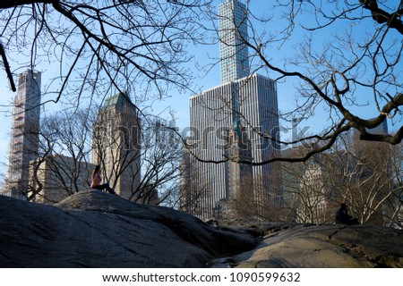 Stock Photo People hanging out in the nice weather on a big rock in Central Park NYC with skyscrapers in the background