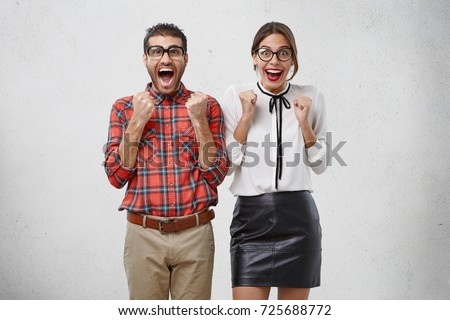 People, happiness and good luck concept. Successful business people in spectacles clench fists with excitment, say yes, express delight as gesturing, rejoice successfully signed contract or agreement #725688772
