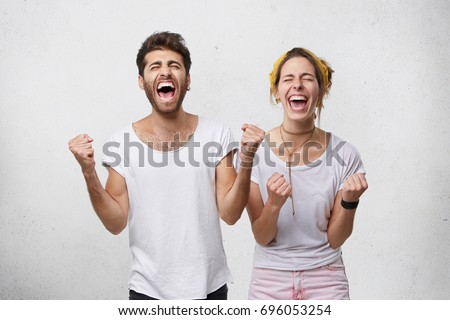 People, happiness, winning, victory, success and good luck. Indoor shot of two young Caucasian people man and woman expressing their excitement and delight by shouting Yes and clenching fists #696053254