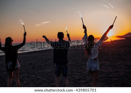 People have fun at night on a beach. Silhouette of friends with firecracker. 4th of July